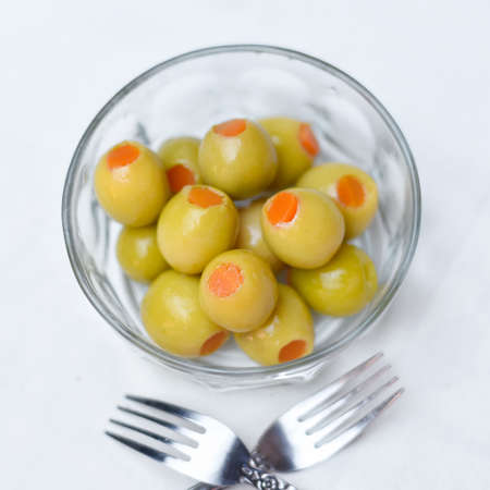 Pickled olives, cucumber, lemon and pepper Homemade organic lightly salted cucumbers Appetizer. Organic, healthy food Eat fresh with a fork Pickled vegetables in plate on the wooden white background