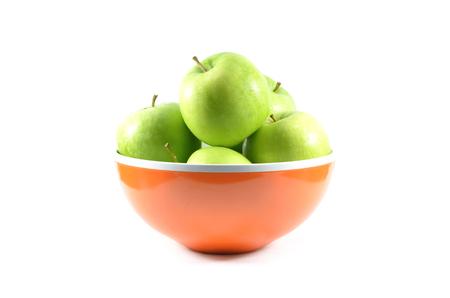 Green apples in orange bowl on white background.