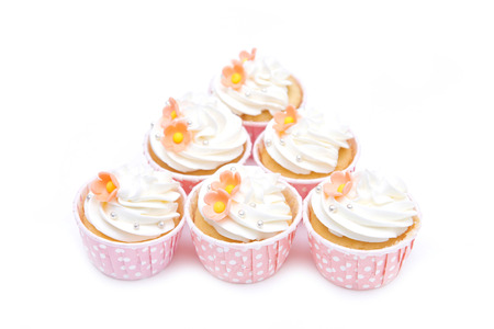 cupcakes isolated: sweet cupcakes and whipped cream in pink cup isolated