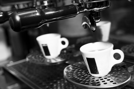 hot espresso in coffee cup on coffee machine in cafe photo