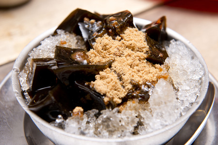 a bowl of black grass jelly on ice with brown sugar,Thai dessert