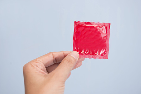 Hand holding condom in red plastic bag photo