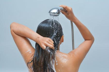 女人洗她的頭髮,淋浴,水 版權商用圖片