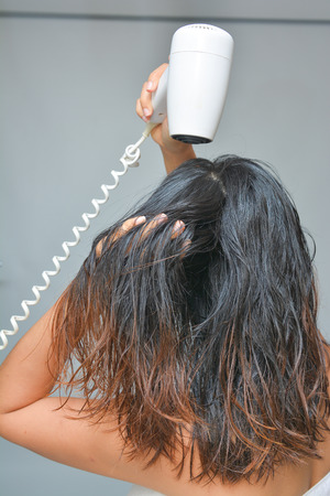 electric dryer: woman is blowing her hair with hair dryer, Electric hair dryer