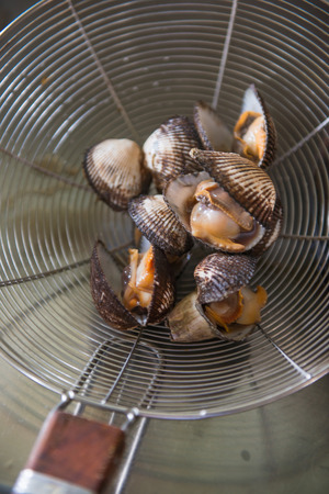 grate: grate fresh boiled cockles, cook Stock Photo