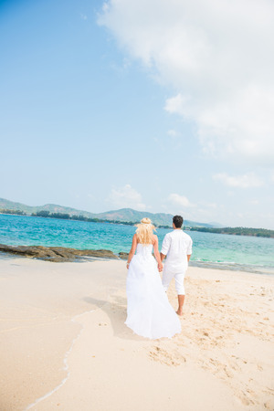 holding  hand: bride and groom are holding hand on beach, lovely