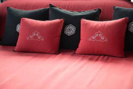 placed: Black and red pillows placed on sofa, cushion