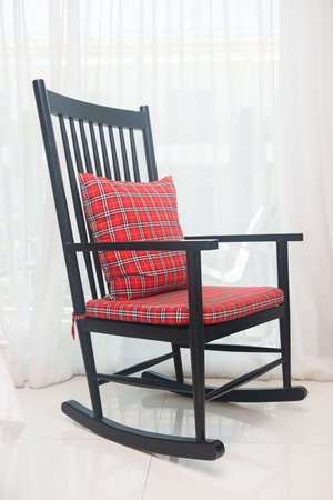red plaid: classic chair with red plaid pillow in living room Stock Photo