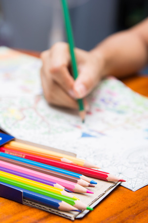 avocation: the girl is painting on coloring books, Wood colors Stock Photo