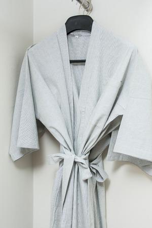 housecoat: gray bathrobe hanging in the closet, clothing