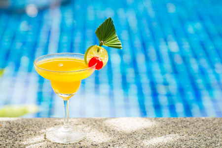 tropical drink: yellow cocktail with lime by the pool, drink