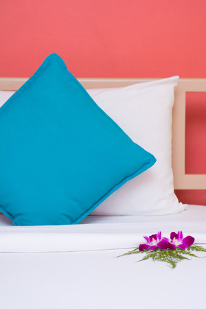 orchid house: white and blue pillows with orange wall background in the bedroom, orchid Stock Photo