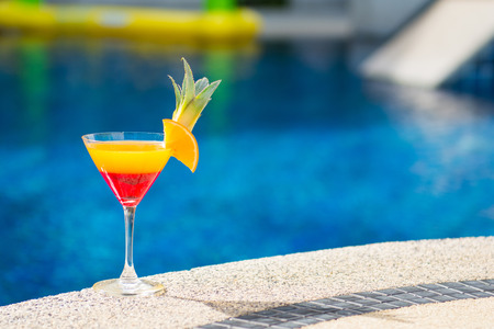 tropical drink: colorful cocktail with orange by the pool, drink