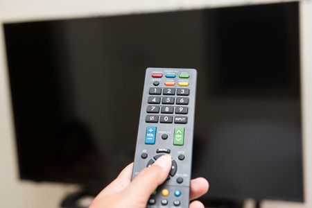 turn on: hand pressing remote control to turn on the TV, television Stock Photo