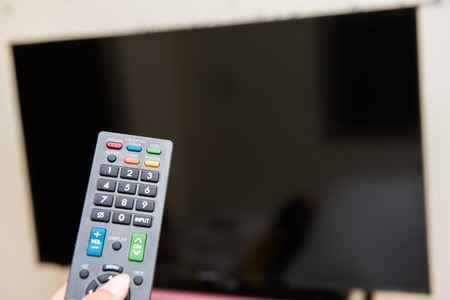 television: hand pressing remote control to turn on the TV, television Stock Photo