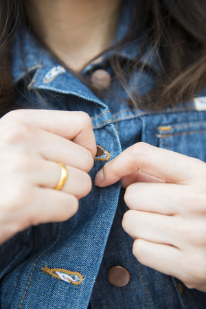 to button up: girl is button up her Denim jacket, wearing