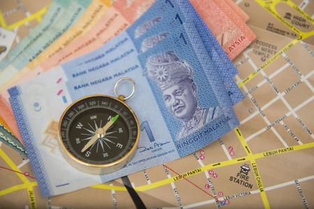 Malaysia money banknotes on map with compass, ringgit