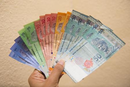 手拿著馬來西亞的鈔票,林吉特 版權商用圖片