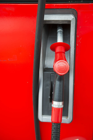 nozzle: red fuel nozzle at gas station, fuel