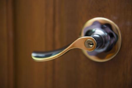 door knob: gold door knob on the wooden door, steel