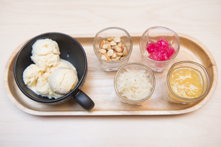 Ice cream served with various topping in small glass on wooden tray, sweet