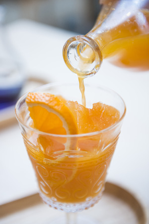 into: womans hand pouring orange juice into a glass, fresh Stock Photo