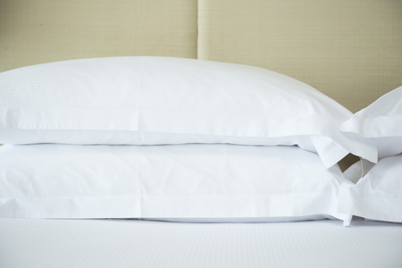 comfortable: comfortable soft pillows on the bed, white