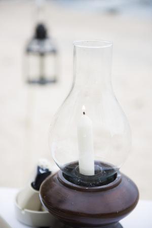 taper: white taper in lantern for dinner set up Stock Photo