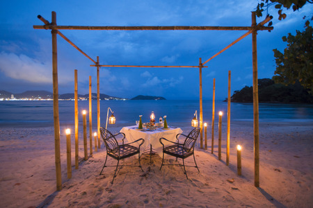romantic beach: romantic dinner set up on the beach, twilight