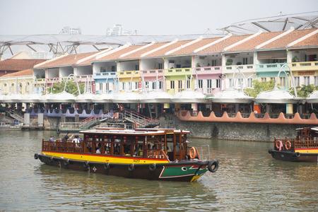 CLARK QUAY, SINGAPORE - OCTOBER 11, 2015: tourist boat cruising the Singapore river at Clarke Quay, Singapore on October 11, 2015, Landmark 新聞圖片