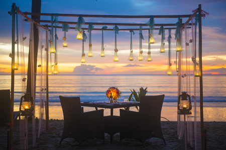 romantic beach: romantic dinner setup on the beach, sunset Stock Photo