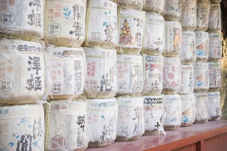 placed: TOKYO, JAPAN - FEBRUARY 21, 2016 : Sake barrels placed stacked on shelf in shrine, Japan on February 21, 2016, culture