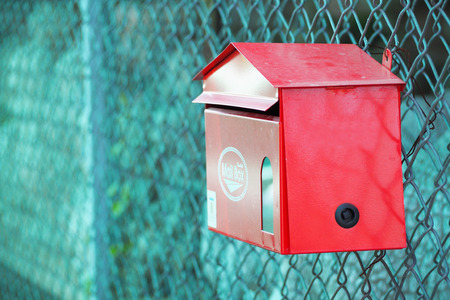 letterbox: red postbox hanging in front of the fence, letterbox Stock Photo