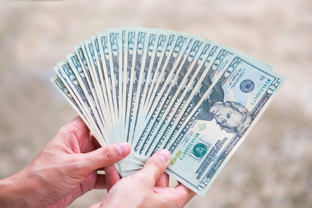 holding money twenty American dollars in hand , cash Stock Photo