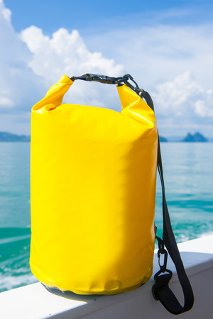 yellow waterproof bag for travel at the sea , protect Stock Photo