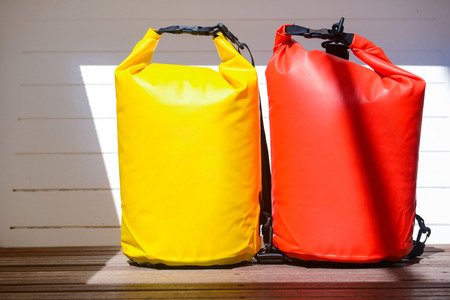 yellow and red waterproof bag for travel at the sea , protect