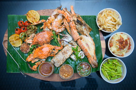 Mixed grilled seafood with side dishes on banana leaf Stock Photo