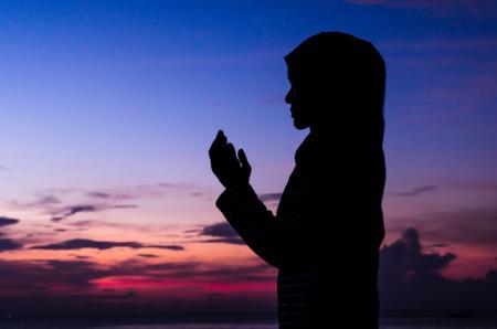mujeres orando: Siluetas de una mujer rezando durante la puesta de sol