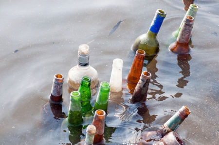 Bad ecology - old bottles float in the river photo