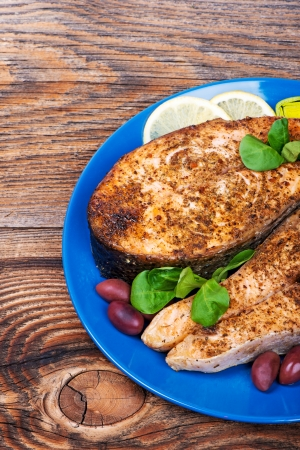 salmon steak with vegetables cooked on the grill photo