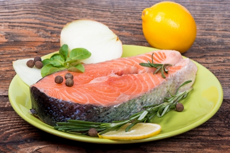 Fresh raw salmon red fish steak with herbs, spices and vegetables photo