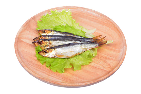 sprat: Smoked fish and salad on a wooden board