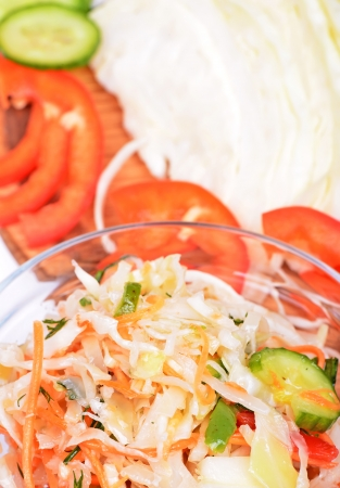 A bowl of coleslaw salad with shredded cabbage and cucumbers, carrots, peppers