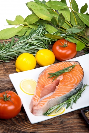 Fresh raw salmon steak with herbs, spices and vegetables photo