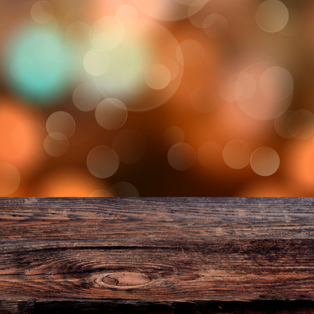 Old weathered wooden board with a sparkling bokeh of party lights in the background