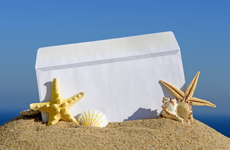 Seashells and starfish with open envelope with blank letter on sand beach photo