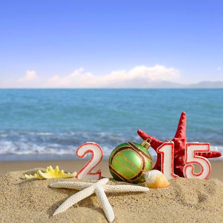 Nieuwe jaar 2015 teken met schelpen, zeesterren en kerst bal op een strand zand Stockfoto