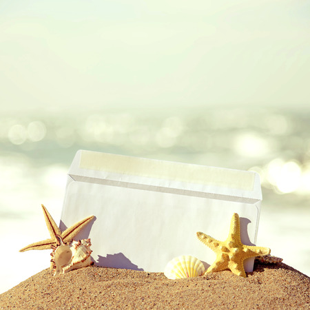 Seashells and starfish with open envelope with blank letter on sand beach. Retro style photo