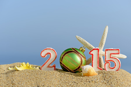 New year 2015 sign with seashells, starfish and christmas ball on a beach sand photo