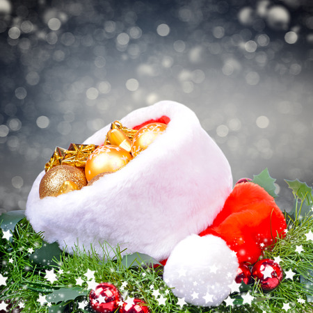 Christmas background with balls, red Santa Claus hat and holly leaves photo
